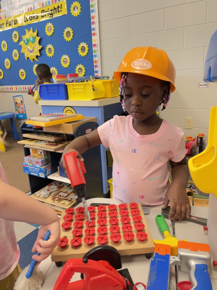 A K4 student dresses up during center time.