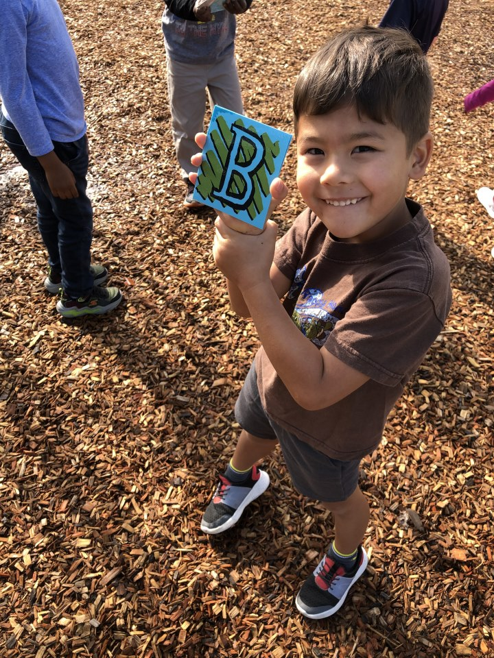 A preschool students finds letter B on the playground.